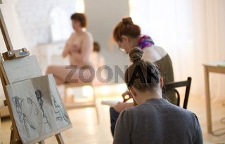 Young female artists sketching a nude model in drawing class