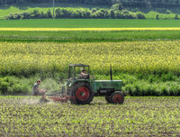 Two farmers on a tractor working in the fields
