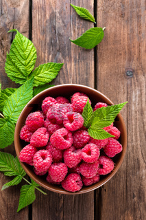 Fresh raspberry with leaves on wooden background