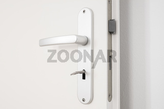metallic door handle with key on white door