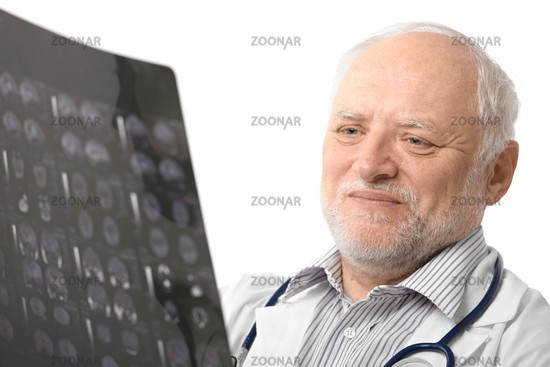 Portrait of senior doctor looking at X-ray image