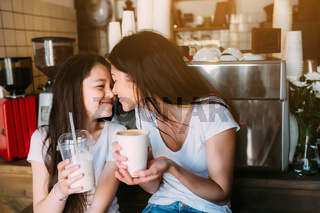 Mother and daughter drink espresso