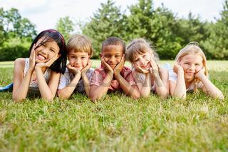 Multikulturelle Kinder liegen im Gras