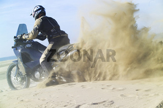 Motorradfahrer mit Staubwolke