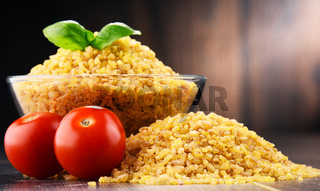 Bowl of uncooked bulgur on wooden table.