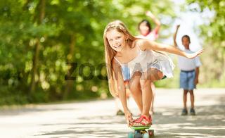 Glückliches Mädchen balanciert auf dem Skateboard