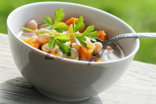 Vegetable soup with bean and carrots on green background