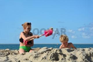 Zwei Kinder spielen mit Schaufeln am Strand und Sand fliegt durch die Luft