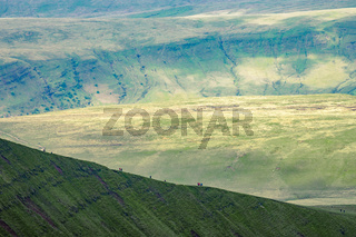People in distance hiking up on the hillside near to Pan Y Fan in Brecon Beacons, Wales