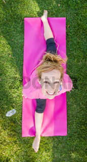 Overhead of Young Fit Flexible Adult Woman Outdoors on The Grass With Yoga Mat Doing The Splits.