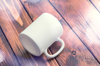 Mockup of white cup laying on wooden table