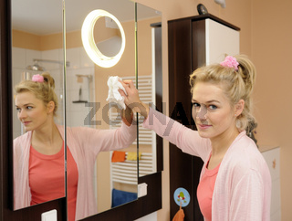 Hausfrau putzt Spiegel im Badezimmer