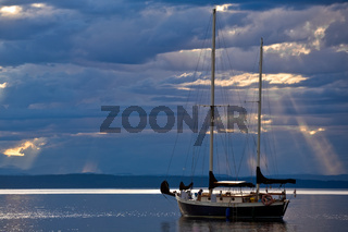 A sailboat on a calm sea at dusk