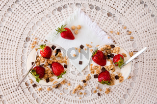 Strawberries cereals and chocolate flakes inside the plain yogurt