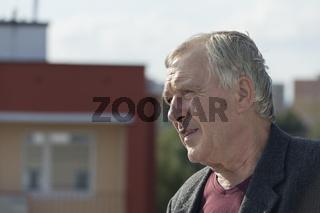 Senior man profile next to the building