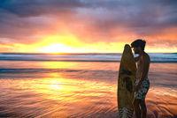 Surfer Views Stunning Sunrise over Ocean
