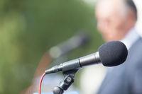 Political campaign. Press conference. Microphone. Speaker. Speech.