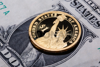 One dollar coin - The Statue of Liberty - on one dollar banknote