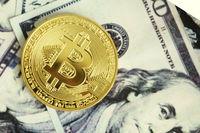 Gold coin bitcoin on hundred dollar bills