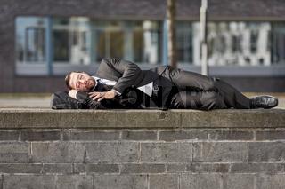 Erschöpfter Geschäftsmann schläft auf einer Mauer
