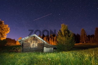 Wooden barn under a starry sky