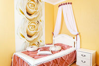 Beautiful bedroom interior with roses and fabric pillows