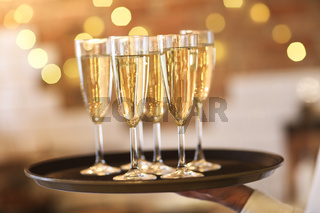 Champagne glasses on tray in bright lights