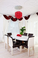 White glossy table with leather chairs in white and red classical interior