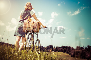 Woman walking with retro bicycle and basket on flower meadow