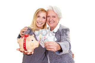 Oma und Enkelin halten Geld und Sparschwein