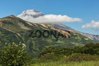 Vilyuchinsky stratovolcano in the clouds. View from brookvalley Spokoyny at the foot of outer north-eastern slope of caldera volcano Gorely.