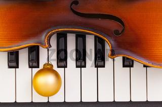Top view close up shot of piano keyboard,old violin and Christmas decoration.