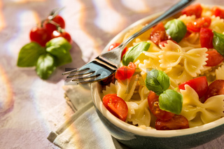 Closeup of Italian Farfalle pasta with tomatoes, basil and fork