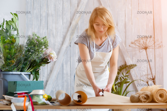 Florist girl cuts wrapping paper