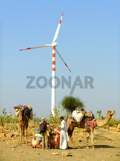 People with camels standing near wind turbine in Thar desert, Rajasthan, India
