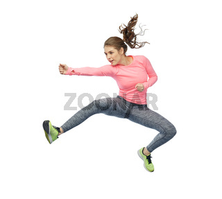 happy sporty young woman jumping in fighting pose