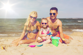happy family playing with sand toys on beach