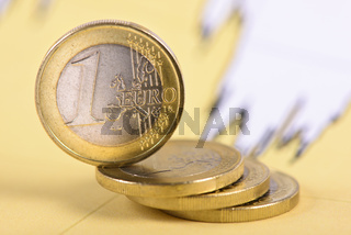 stacked euro coins laying on financial business chart of stock market
