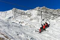 Skifahrer auf einem Sessellift vor dem Feegletscher und dem Dom Gipfel,Skigebiet Saas-Fee, Schweiz