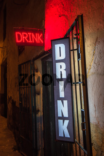 Drink neon sign at the entrance of a bar