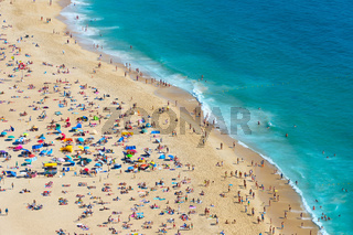 Crowded ocean beach. Nazare, Portugal