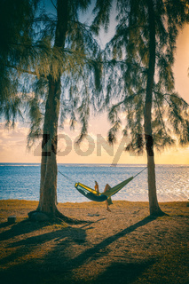 Silhouette of woman reading in hammock