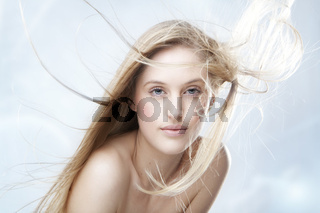Fashion portrait of a beautiful blonde girl with hair fluttering in the wind