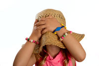 Girl pulling straw hat over her head