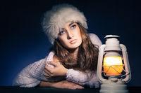 beautiful woman sitting with lantern over dark