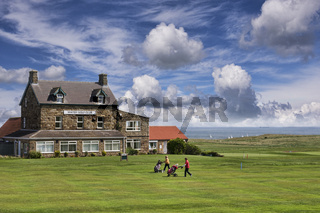 Two lady golfers walk in front of Whitby Golf Club with their golf trolleys