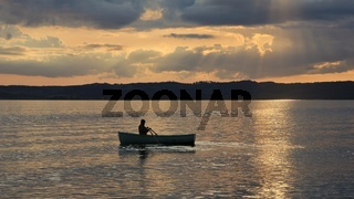 Summer sunset in Ebeltoft, Denmark. Man rowing in a small boat.
