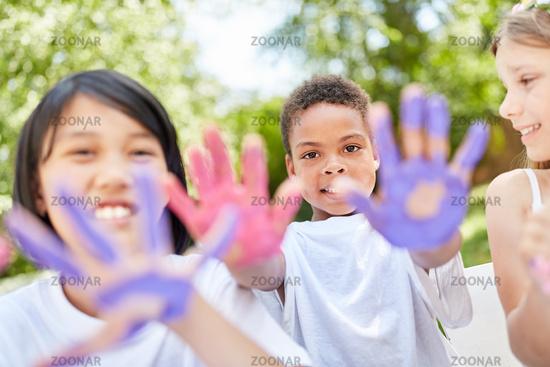 Kinder im Kindergarten malen mit Fingerfarben