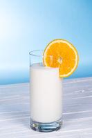 Glas Milch mit Orangen Scheibe auf hell blau Hintergrund.