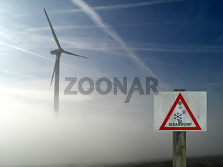 Windrad im Nebel mit Gefahrzeichen